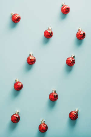 Red Christmas balls ornaments on blue background. Flat lay, top view. Minimal style.