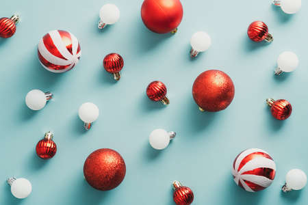 Red and white Christmas balls decorations on blue background. Flat lay, top view. Christmas greeting card design.