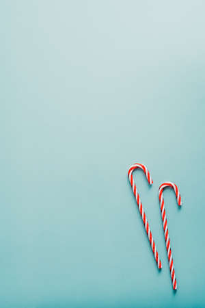 Striped Christmas Candy Canes on blue table top view. Flat lay. Standard-Bild