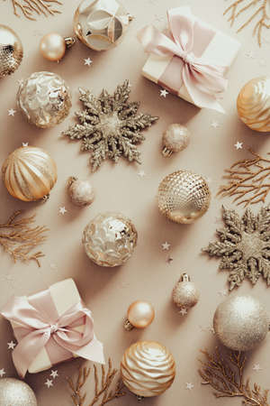 Golden Christmas decorations, gift boxes, snowflakes on beige background. Flat lay, top view.