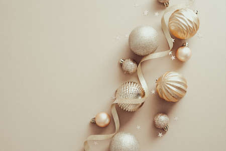 Stylish Christmas baubles and ribbon on beige background. Flat lay, top view. Standard-Bild