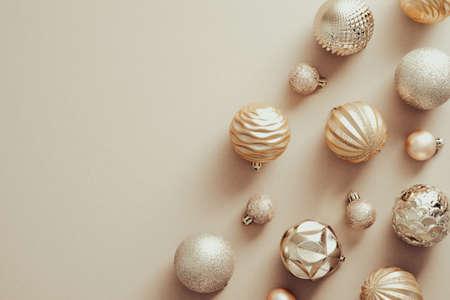Golden Christmas balls decorations on beige background. Elegant Xmas banner design, New Year greeting card mockup Standard-Bild