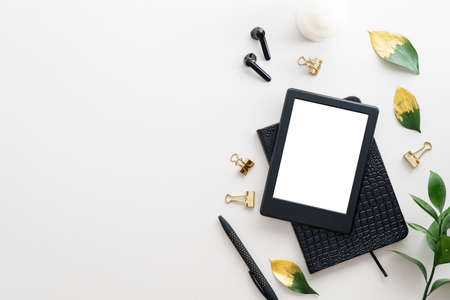 E-reader digital tablet, paper notebook, pen, plant leaves on white table top view. Distance learning concept.