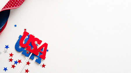 Happy Veterans Day banner design. USA decorations, confetti, ribbon on white table. Flat lay, top view. Standard-Bild