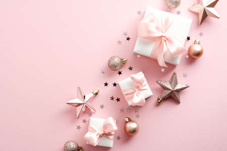 Elegant Christmas composition with gift boxes, decorations, stars, confetti on pastel pink background. Flat lay, top view, overhead.