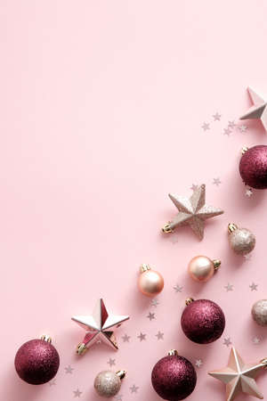 Christmas holiday flat lay composition with Xmas decorations, balls, stars on pink background. Elegant, minimal style.
