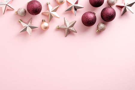 Pink Christmas background with glittering stars and baubles. Flat lay, top view. New Year banner design with elegant decorations.
