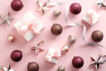 Christmas holiday flat lay composition. Top view gifts, balls, decorations on pastel pink background. Standard-Bild