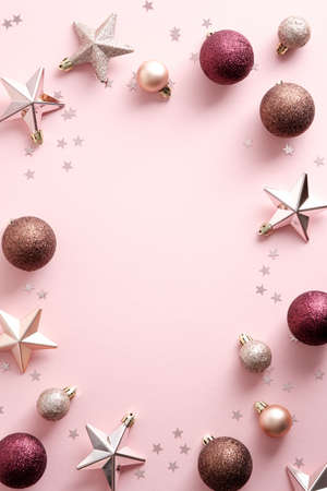 Christmas frame with stylish decorations, stars, balls, confetti on pastel pink background. Flat lay, top view, overhead. Standard-Bild