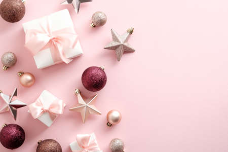 Christmas composition. Elegant Christmas decorations, baubles, gift boxes on pastel pink background. Flat lay, top view, overhead.