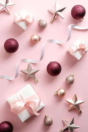 Christmas flat lay composition. Christmas pink decorations and gift boxes on pastel pink background.