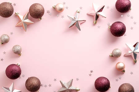 Christmas frame with decorations, balls, stars, confetti on pink background. Flat lay, top view, copy space. Elegant, minimal style.