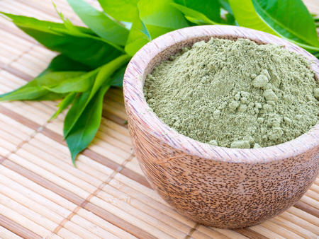 Henna powder in the coconut bowl on the green leaves background