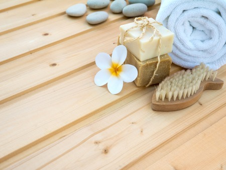 nail brush: White rolled towel, tiare flower, soap tied with jute rope, stones and fish shaped nail brush on the wooden planks