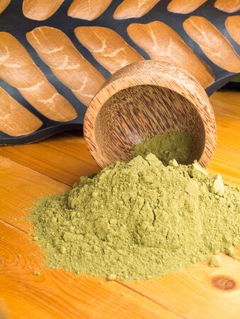 colorant: Henna powder hair colourant in the coconut bowl on textured wooden background
