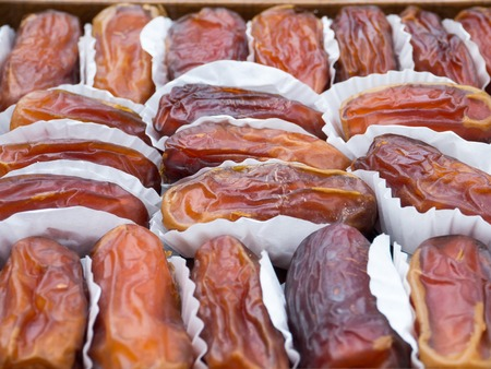 closely: Dried dates in the paper wrappings arranged closely to each other