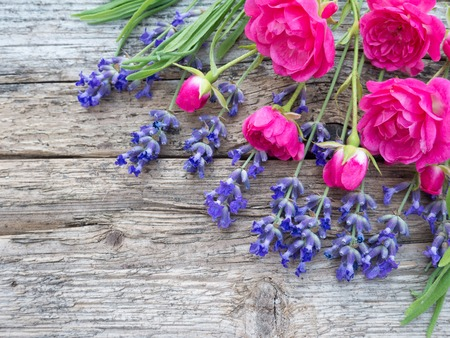 Small vibrant pink roses and provence lavender bouquet on the old weathered wooden board