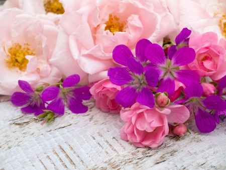 pale background: Pale pink and small bright pink roses and geranium bouquet on the white rough wooden table Stock Photo