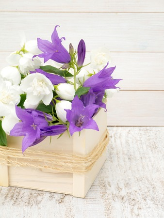 philadelphus coronarius: English dogwood and bellflowers bouquet in the wooden box tied with jute rope