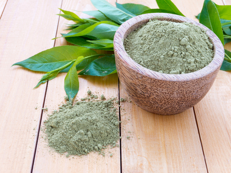 colorant: Henna powder pile and green leaves on the wooden background
