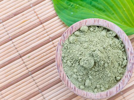 colorant: Henna in the coconut bowl and green leaf on the bammboo mat