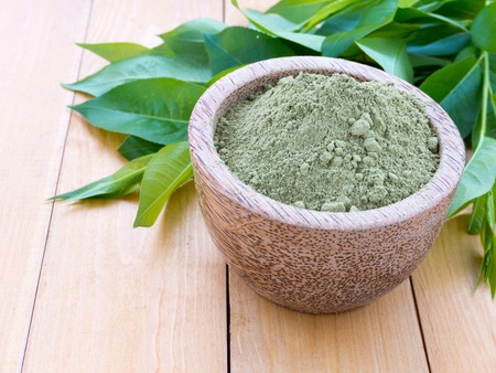 Henna safe hair dye powder and green leaves on the wooden table Standard-Bild