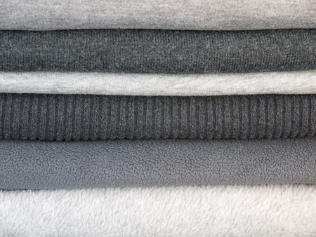 Stack of winter clothes in different shades of gray