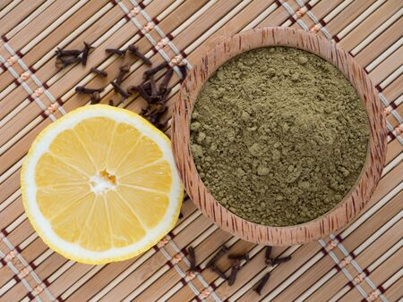 Henna powder and lemon on the bamboo mat background