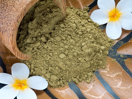 Tiare flowers and henna powder in coconut bowl