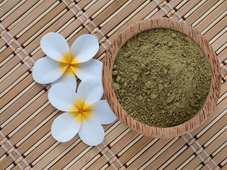Henna powder in coconut bowl on the bamboo mat Stock Photo