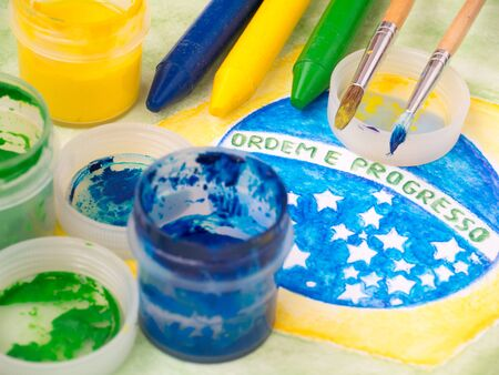 motto: Paint in jars,lids,brushes and crayons on the brazil flag watercolor painting.  Motto on the flag Ordem e Progresso (portuguese Order and Progress).