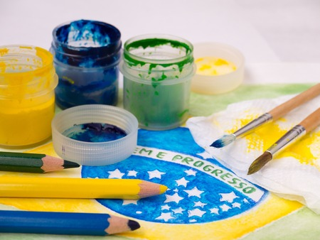 motto: Paint in jars,lids,brushes and pencils on the brazil flag watercolor painting.  Motto on the flag Ordem e Progresso (portuguese Order and Progress).