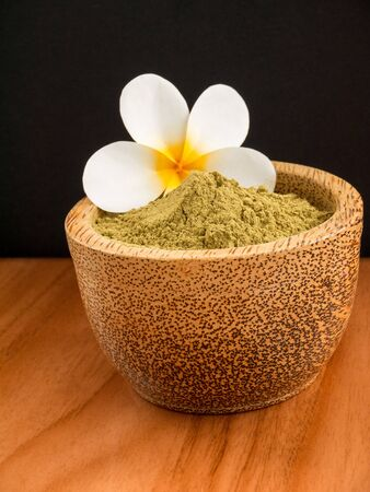 Henna powder in coconut bowl with tiare flower