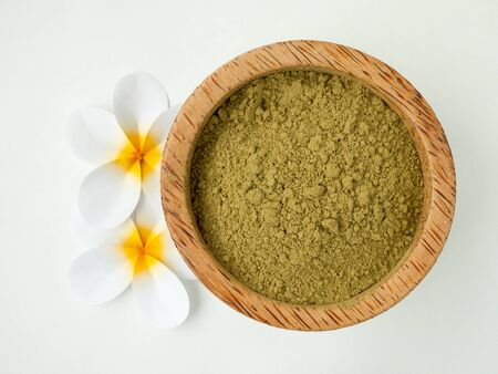 Henna powder in coconut bowl and tiare