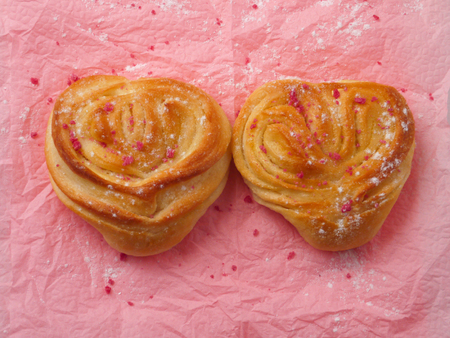 san valentin: Two heart shaped buns on the pink background Stock Photo