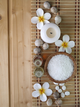 Shells,massage oils and tiare flowers on the wooden background