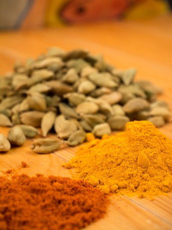 cardamon: Colorful cardamon,  turmeric and pepper piles on the blurred background Stock Photo