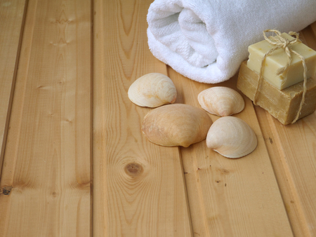 relaxation background: Towel,soap,and shells on the wooden background Stock Photo