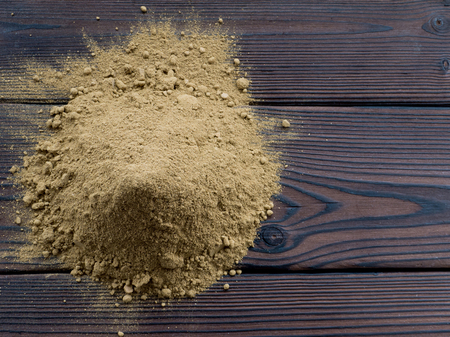 colorant: Henna powder pile on the dark wooden planks top view