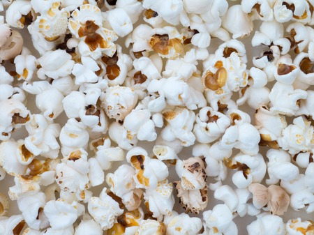 popped: Popped corn grains on the paper background Stock Photo