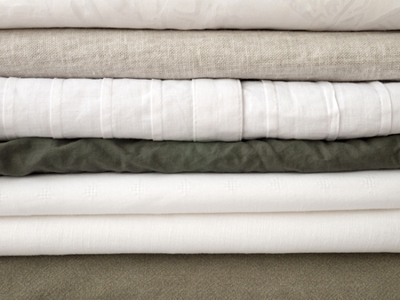 Stack of cool summer white and khaki clothes with different textures