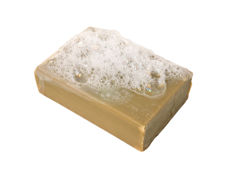 lather: Natural olive oil soap bar with lather isolated on white