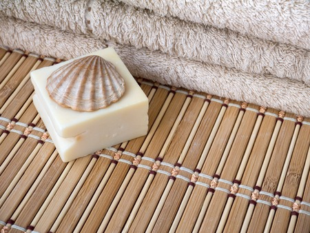 scallop shell: Natural milk soap bar, scallop shell and terry towel on the bamboo mat Stock Photo