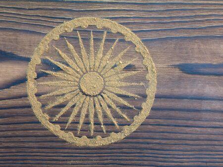 ashoka: Indian henna powder in the form of Ashoka Chakra on the textured wooden board