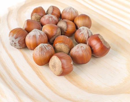 cobnut: Pile of hazelnuts in nutshells on the wooden background