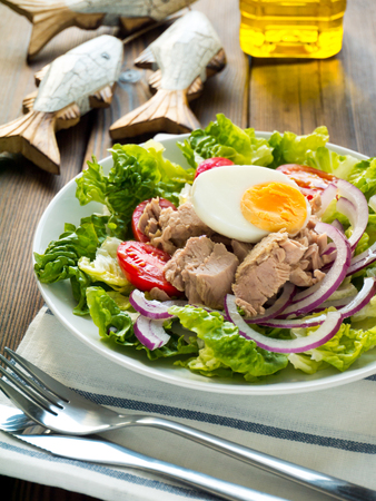 Tuna salad with lettuce leaves, cherry tomatoes, egg and sweet onion on the dark wooden rustic table