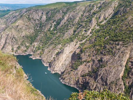 Catamaran in the canyon of Sil river in the province of Ourense, Galicia, Spain. Ribeira Sacra deep canyon landscape view from Vilouxe viewpoint.