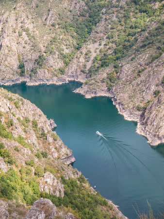 Excursion boat in the canyon of Sil river in the province of Ourense, Galicia, Spain. Ribeira Sacra deep canyon landscape view from Vilouxe viewpoint. Stock fotó