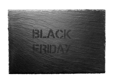 Black friday stencil on the dark gray slate plate isolated on white. Bargain sale concept.  Imagens