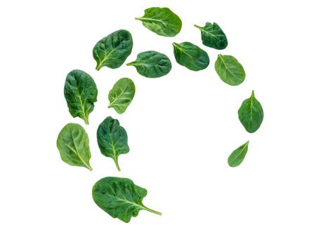 Spiraalvormige vliegende hoop van groene die spinaziebladeren op wit wordt geïsoleerd Stockfoto
